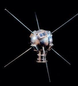 """Satélite de forma circular com uma base cilíndrica de cor metálica puxada para o prata. Seis antenas saem do círculo como se fossem espinhos, e são antenas de comunicação. Na face visível do círculo, é possível identificar um painel fotovoltaico retangular, que lembra uma janelinha no satélite. Link no post """"Energia Solar e o Espaço""""."""