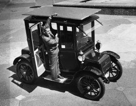 Foto de uma carro antigo com um homem em pé na porta do passageiro, que está aberta. Ele aponta para o teto do carro, no qual está um painel solar que cobre o carro em toda sua extensão.
