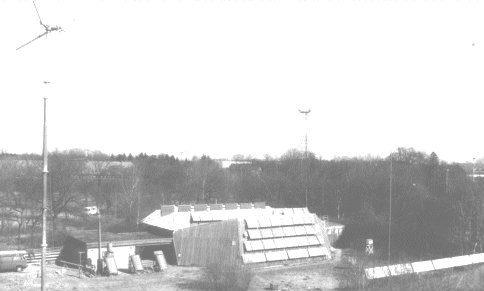 Foto aérea P&B de um prédio com cerca de dois ou três andares em meio a vegetação e outros prédios menores.