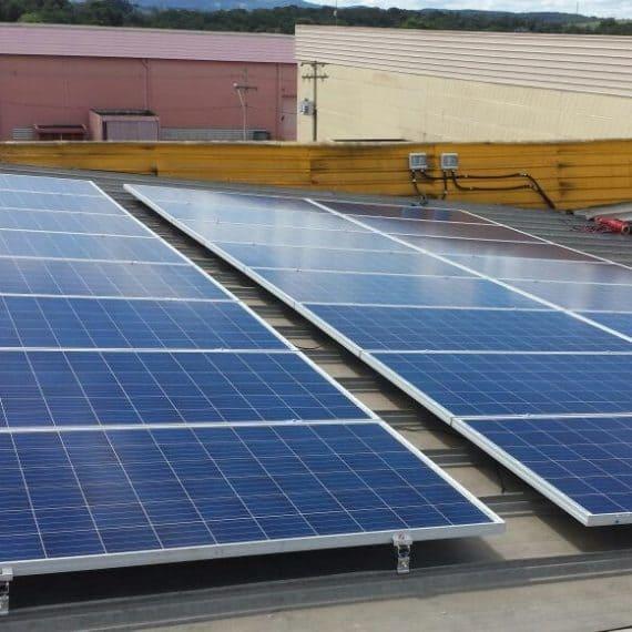 Foto de três fileiras longas de paineis fotovoltaicos no projeto comercial da AES. O sistema está no telhado.