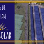 Foto aérea de um sistema fotovoltaico bem grande, a nível de usina, localizado entre uma grande avenida e algumas quadras poliesportivas.