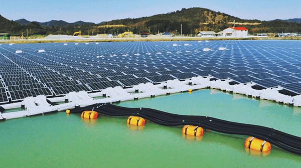 Foto de uma superfície grande de água com diversos painéis fotovoltaicos instalados em estruturas brancas parecidas com plástico. Ao fundo, uma colina coberta por vegetação. Usina flutuante da Kyocera.