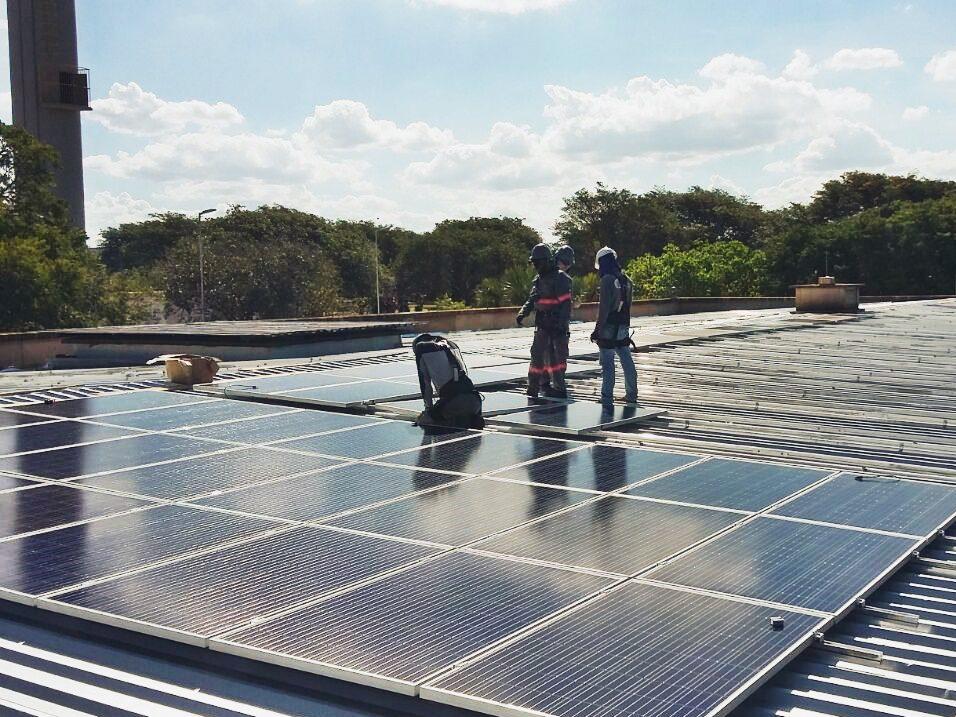 Três fileiras de painéis fotovoltaicos instalados em uma telhado de galpão industrial. Ao lado da fileira do topo, estão três homens trabalhando na instalação dos painéis. Foto do projeto comercial de Bauru I.