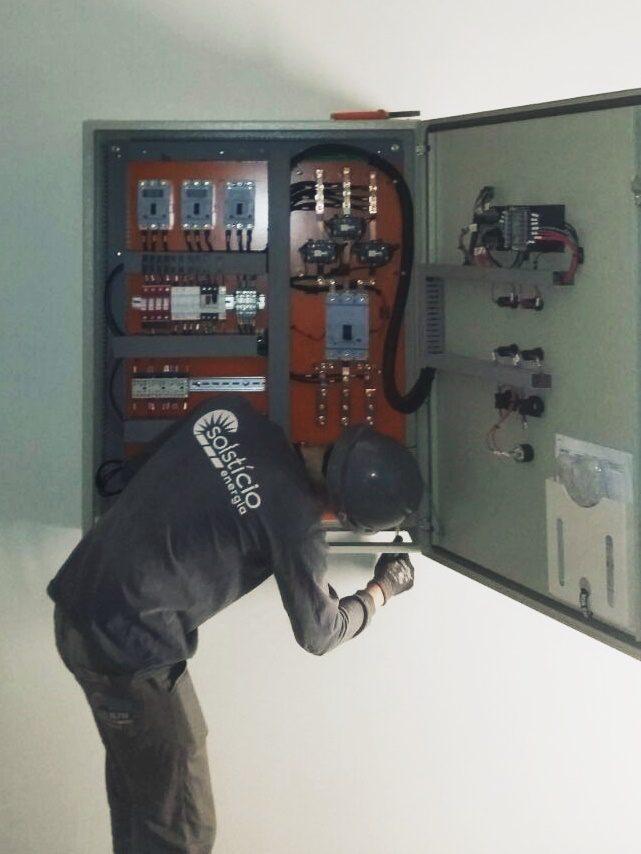 Foto tirada da caixa de energia aberta com um técnico mexendo nela. O técnico usa uniforme e capacete cinza.