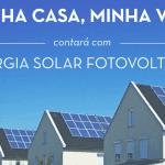 """Foto do topo de três casas, nas quais pode-se ver o telhado igual para as três. No telhado, um sistema fotovoltaico de três fileiras com 8 paineis casa. Na porção superior da imagem, ao fundo do céu azul, o texto """" Minha Casa Minha Vida contará com energia solar fotovoltaica""""."""