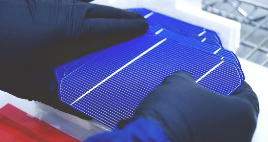Foto de duas mãos cobertas com uma luva preta segurando uma célula solar padrão (quadrada, azul escuro com algumas listras prateadas))