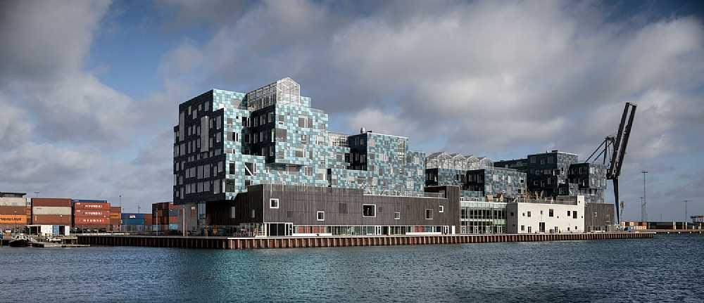 Foto tirada por Adam Mørk que mostra a Escola Internacional de Copenhagen em sua totalidade, podendo ver de longe o edifício todo. Os paineis fotovoltaicos de diferentes cores chamam atenção nessa que é uma das construções solares mais conhecidas atualmente.