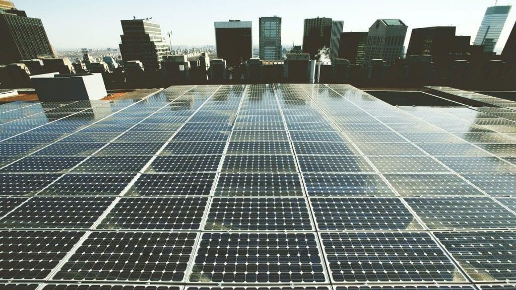 Foto de paineis fotovoltaicos em um telhado no cenário urbano de nova york; post sobre microrrede solar.