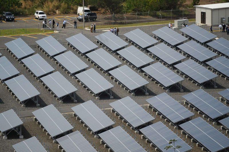 Foto de diversos painéis fotovoltaicos instalados no chão, como uma usina, complementando o post sobre aumento da geração distribuída no país.