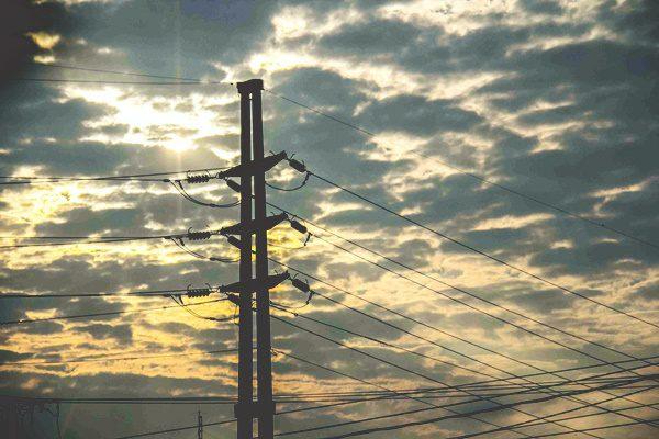 Foto de uma torre de energia com um céu de fim de tarde cheio de nuvens. Apresentação do texto sobre a compensação de energia entre concessionárias.