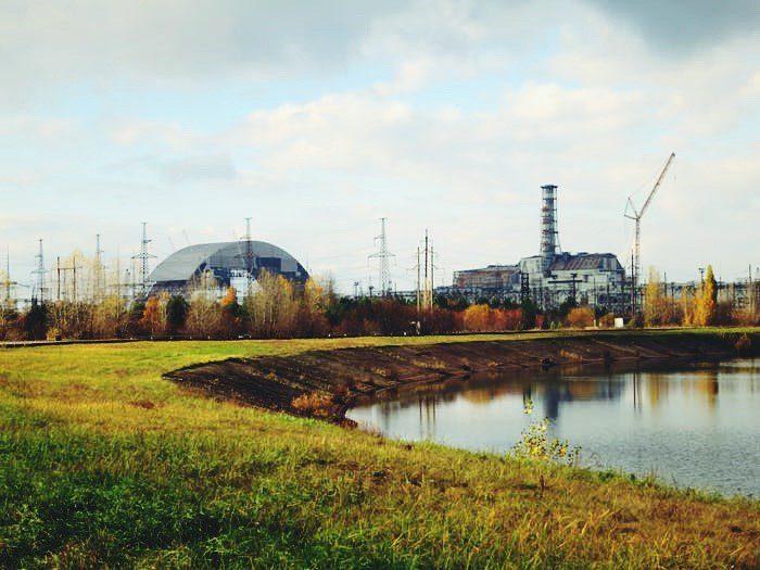 Foto tirada de uma paisagem abandonada de Chernobyl com bastante grama e prédios deteriorados