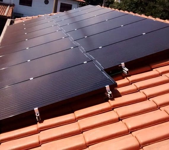 Foto de duas fileiras curtas de painéis fotovoltaicos bem escuros organizados em um sistema fotovoltaicos.