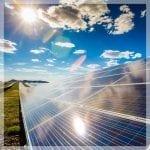 Foto tirada a nível da visão de um longo módulo de paineis fotovoltaicos, indo até o horizonte. Essa parte que mostra o painel está na porção direita do quadro da foto. Ao fundo, um céu azul. Na porção mais à esquerda, um gramado bem verde. Link no post sobre impactos da energia solar fotovoltaica no meio ambiente.