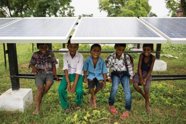 Foto de um sistema fotovoltaico instalado no solo. Abaixo dos paineis e sentados na estrutura metálico do sistemas, estão cinco meninos sorridentes.
