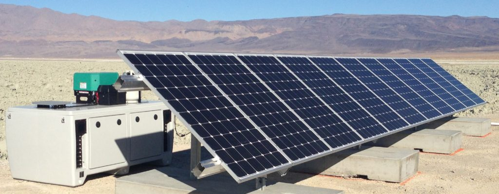 Conjunto de paineis fotovoltaicos instalados no chão em uma paisagem desértica com montanhas rochosas ao fundo. Atrás do sistema, um tipo de cabine protege as baterias do sistema.