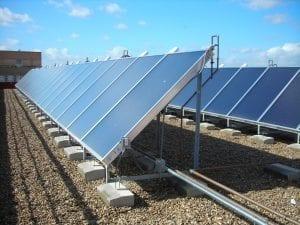Conjunto de paineis solares térmicos instalados no solo com uma estrutura metálica. A foto foi tirada na diagonal da cena, na altura média de um observador. É possível ver duas fileiras de aproximadamente dez paineis cada. Ao fundo, céu azul. Foto no post de energia solar térmica e fotovoltaica.