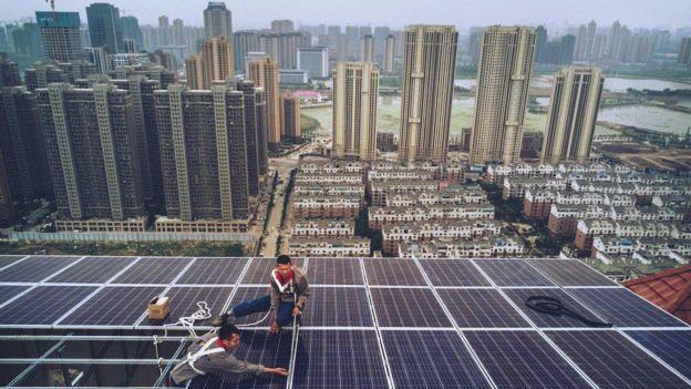 energia solar china; foto de dois instaladores com um sistema fotovoltaico; ao fundo, paisagem urbana.