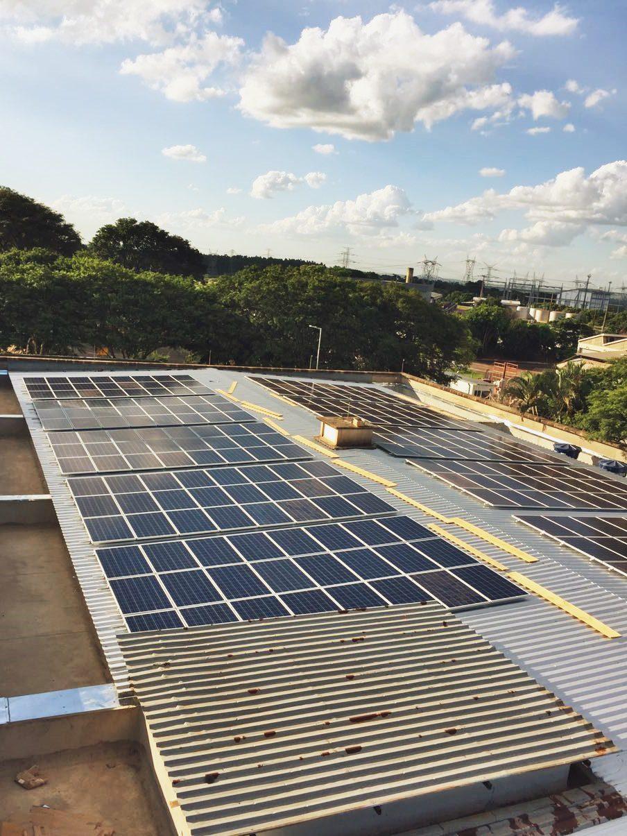 Foto tirada de longe do telhado de um galpão industrial. Ele está quase que totalmente coberto por painéis fotovoltaicos. Ao fundo, na paisagem, um conjunto de grades árvores, uma porção de cidade e o céu azul claro.