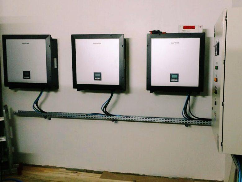 Três inversores instalados lado a lado em uma parede.