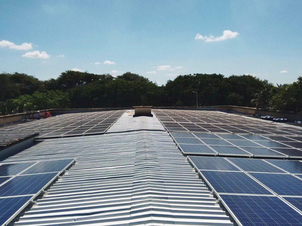 Foto tirada ao centro de um telhado de uma galpão, mostrando fileiras de paineis das extremidades esquerda e direita do telhado.