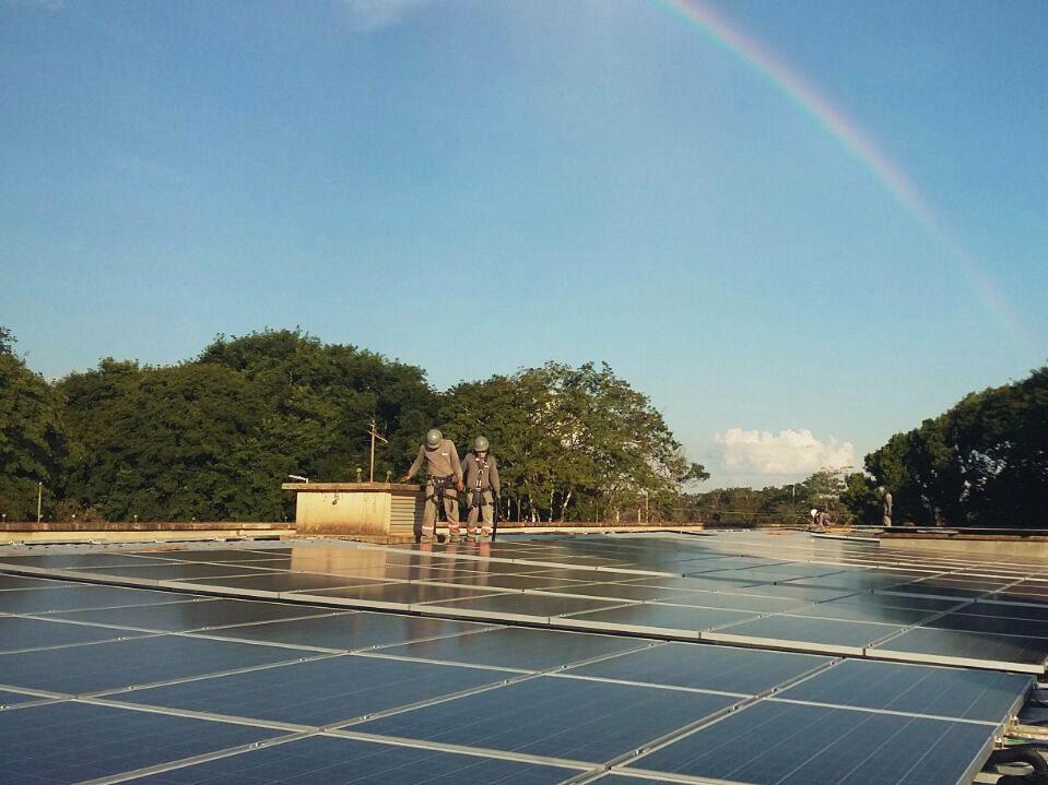 Foto tirada a nivel dos paineis que mostra uma grande superfície coberta por painéis fotovoltaicos. Ao fundo, dois homens em pé andam próximos aos painéis, o céu é azul claro e há um arco-íris.