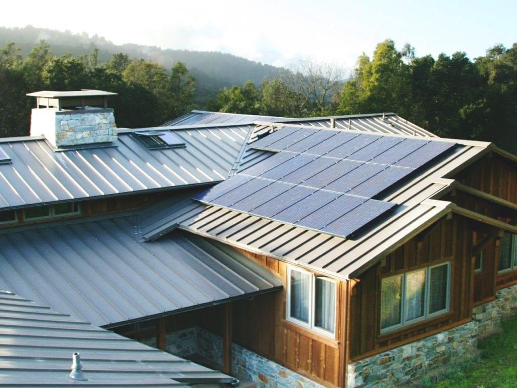 Foto com foco no telhado de uma casa, composto por diversas águas. Em uma delas, pode-se ver um sistema fotovoltaico de três fileiras, totalizando 22 painéis. Um exemplo de geração distribuída, onde a energia é produzida a nível local.